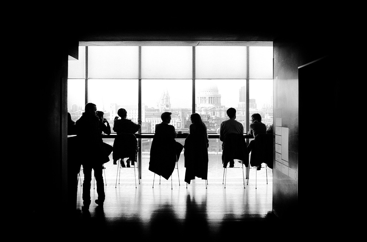 Silhouette of people sitting around a boardroom table