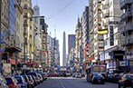 Buenos Aires street lined with cars and obelisk in the background