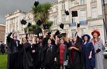LLM in Paris students throwing graduation caps after ceremony
