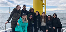Energy Law students standing next to wind turbine at an ocean windfarm