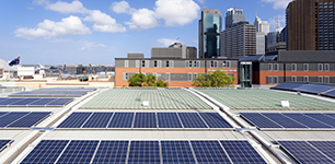 Solar panels on a roof in a city with skyscrapers in the background