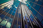 View of a glass office building from the ground up with the cloudy blue sky reflected on the surface