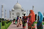 Women in traditional Indian dress walking in front of the Taj Mahal