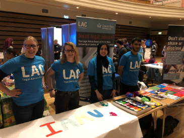 Four people stand at an exhibition table. They are wearing LAC t-shirts.