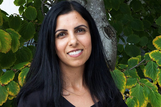 An image of Professor Renisa Mawani. She stands outdoors with a tree and foliage behind her. She has light brown skin, brown eyes, long straight black hair and wears a black v-neck top. She is smiling.