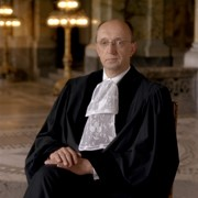 A picture of Judge Peter Tomka he is seated with his hands in his lap and is wearing court dress.
