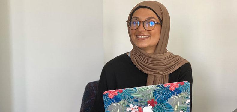 Assia Al Jerrari holding a laptop