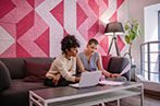 A black woman and a white woman sat in office with pink patterned wall paper