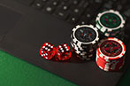Poker chips and a dice sitting on a laptop keyboard