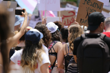 A group of women at a protest seen from behind. In the distance, ahead of them there are signs and placards.