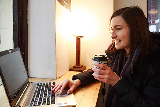 Student in a cafe reading from a laptop