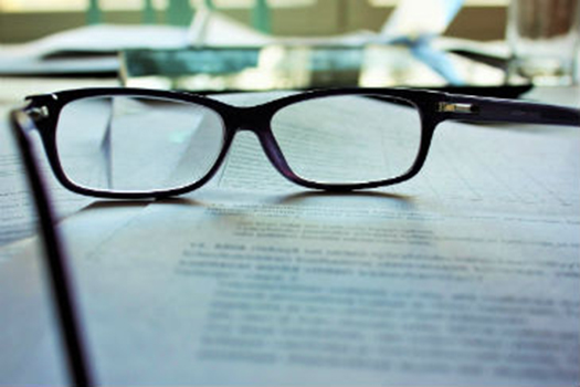 Pair of glasses on some academic papers