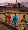 Four Indian women walking along a a field by a factory