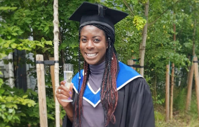 Christine Ohuruogu stands in graduation gown and cap holding her a glass of champagne. She has dark skin and long black and auburn braids.