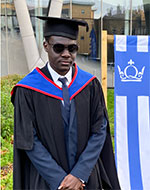 Umar Geidman standing outside Queen's Building in graduation robes