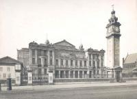Black and white photograph of the front of the People's Palace in Mile End in the early twentieth century showing a cobbled street, clock tower, a large stone building, the winter garden to the right, st benets church to the left and posters for events on a notice board