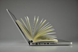 Colour image of an open laptop with an open book sitting inside it
