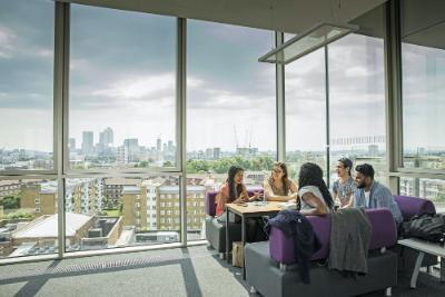 Students chatting in the Graduate Building with a view of the London skyline