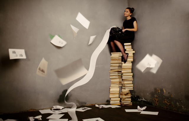 Stock image of a woman sitting on a pile of books whilst typing