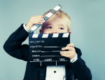 Photograph of a child with clapperboard
