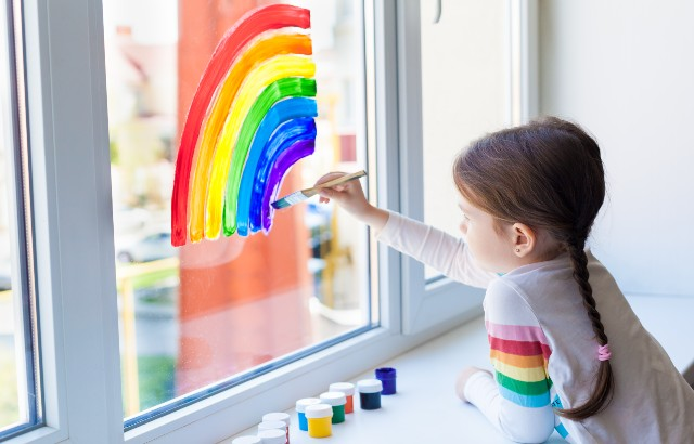 A child girl paints a rainbow on a window during the quarantine for the coronavirus pandemic.