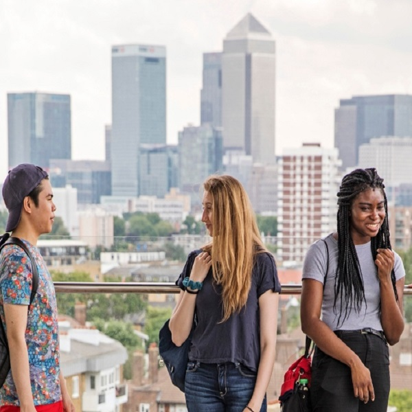 Three students talking with the background of London buildings.