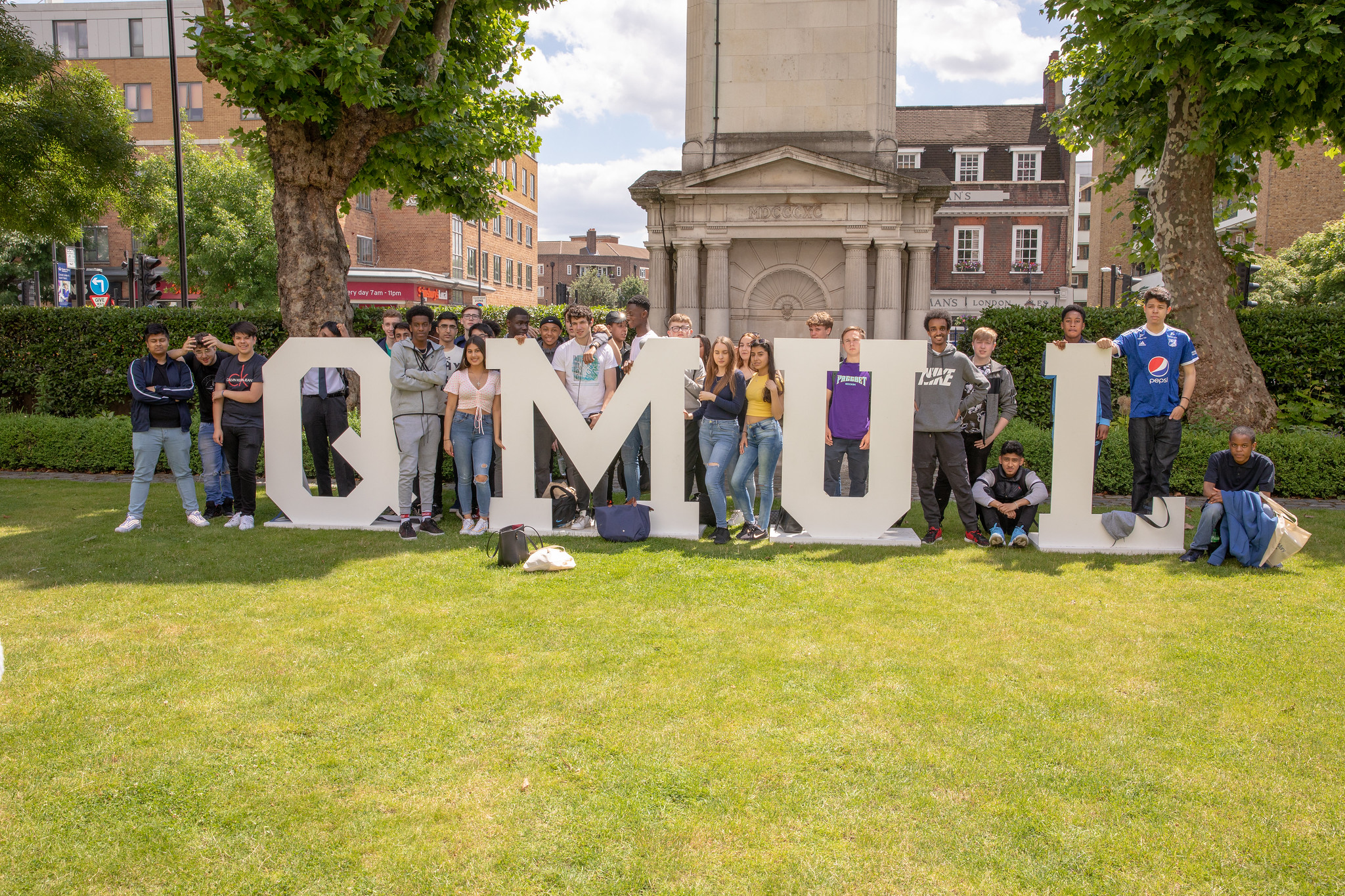 Students on the lawn with QMUL letters