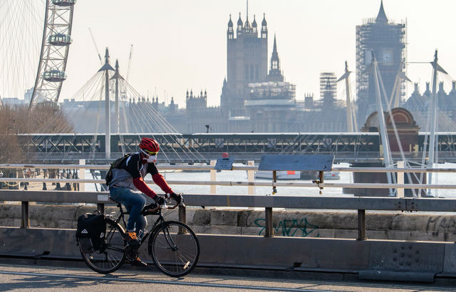 A cyclist wearing a facemask cycles past Parliament
