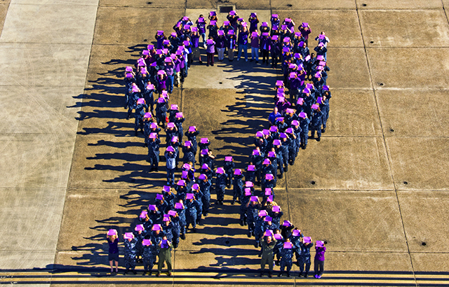 People form a purple ribbon to raise awareness for domestic violence