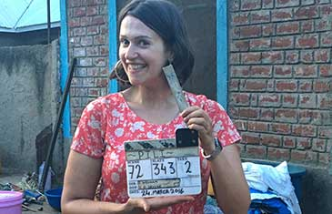 Sophie Harman with a clapper on the film set of PILI