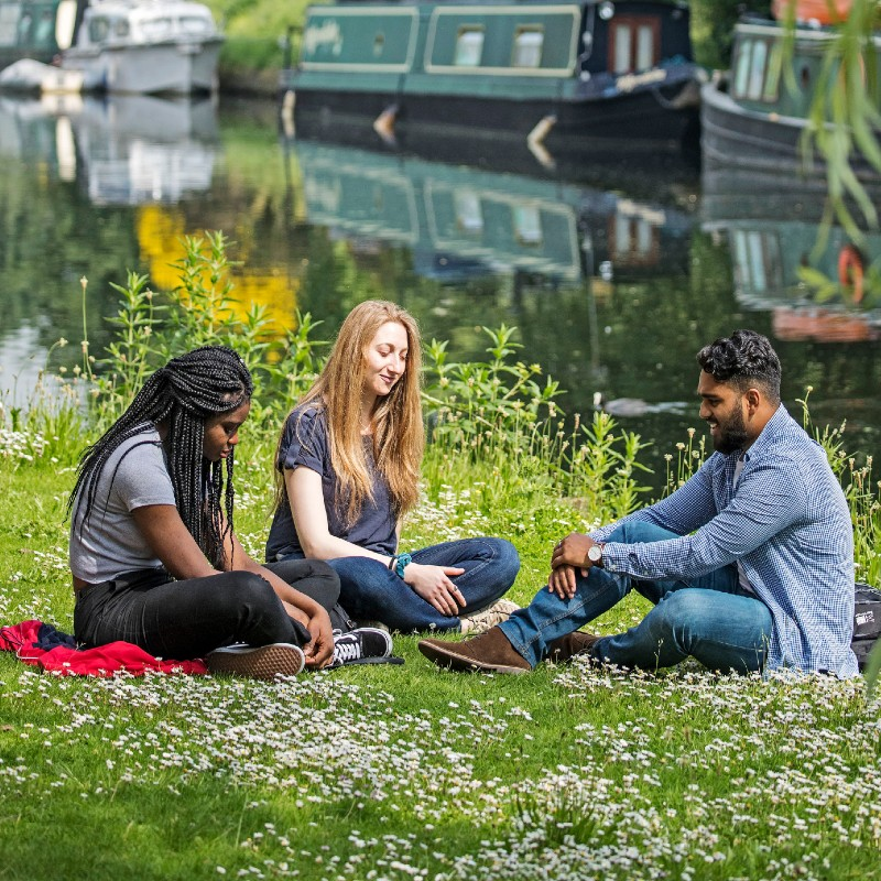 3 students sitting on the grass by the canal