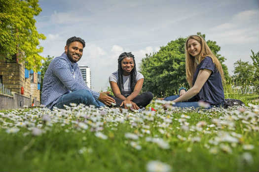 Queen Mary University of London students sitting on the grass at our Mile End campus