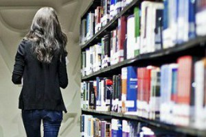 student walking alongside library shelf