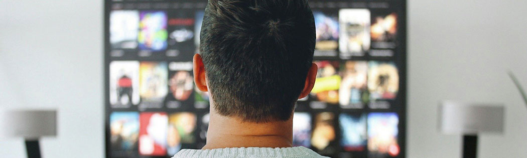 View of the back of a person's head, they are browsing a streaming service in the foreground