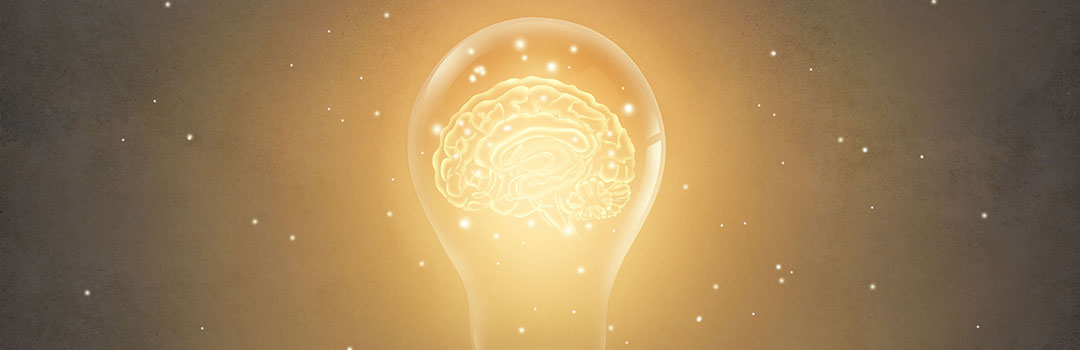Lightbulb emitting a yellow light with a brain inside