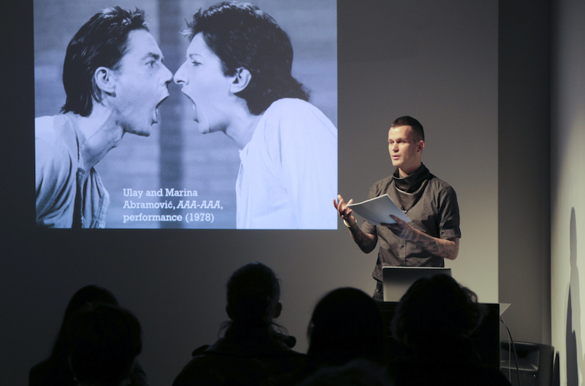 Dominic Johnson gives a lecture backed by a slide showing a performance by Ulay/Abramovic