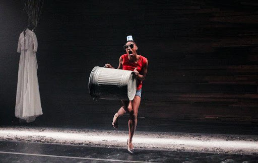 A performer dances carrying a large metal rubbish bin
