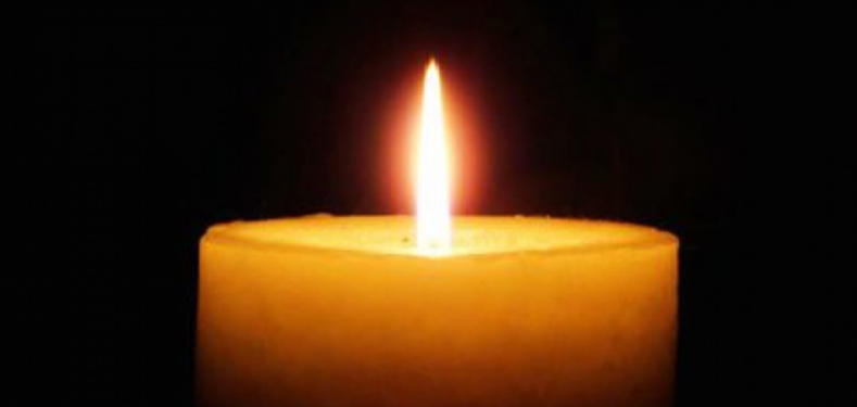 A single lite candle on a black background